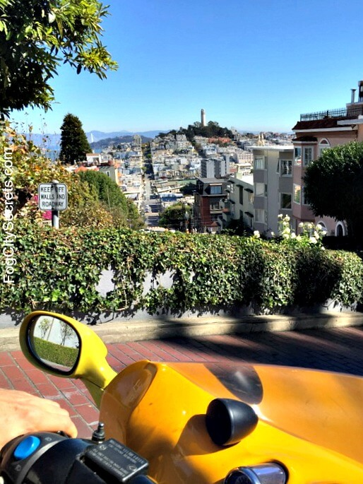going down lombard street in a go car, view of coit tower