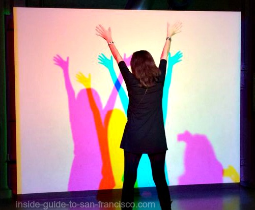 Woman creating colorful shadows, Exploratorium