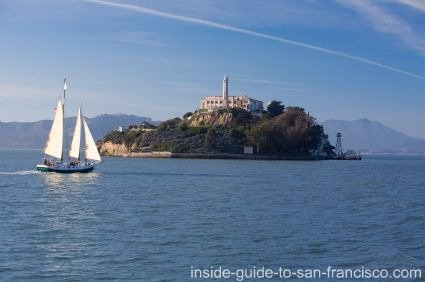 View of Alcatraz Island and prison, with a sailboat on the bay.