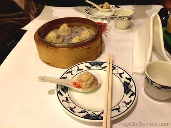 Tablel at Yank Sing Restaurant, two plates and dish of soup dumplings.