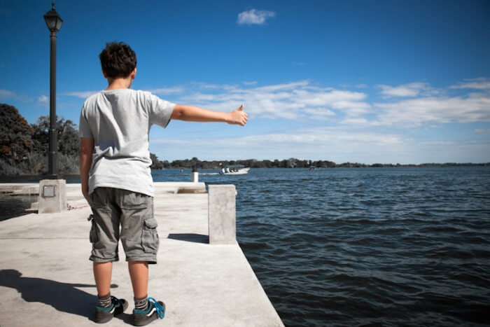 Little boy trying to hitchhike at an empty boat dock.