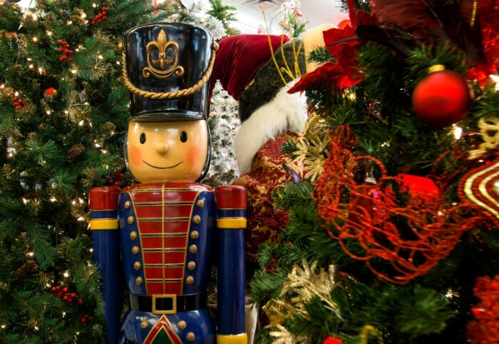 Wooden Nutcracker In Front Of Decorated Christmas Tree