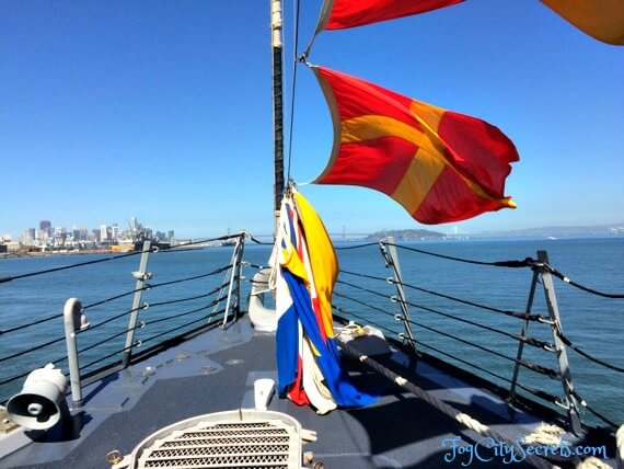 Flags flying on deck of SF Fleet Week navy ship during ship tour.