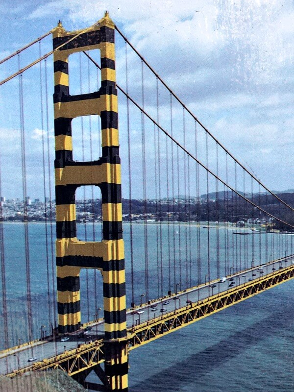 Image of Golden Gate Bridge with black and yellow striped paint job.