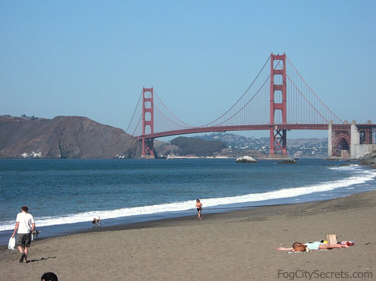 View of Golden Gate Bridge and sunbathers at western end of Baker Beach.