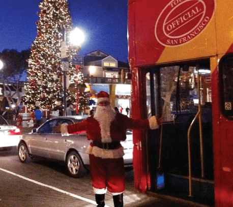 Guide on Holiday Lights Tour dressed as Santa, beside tour bus at Pier 39