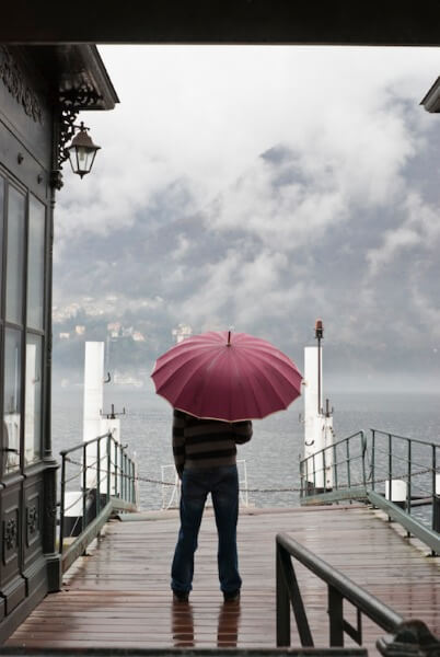 Man on stormy dock with umbrella.