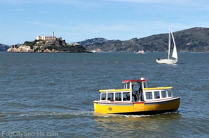 Little, yellow San Francisco water taxi traveling, with Alcatraz in background