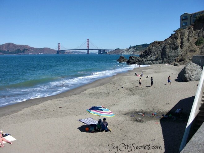China Beach, sunbathers on beach and Golden Gate Bridge view.