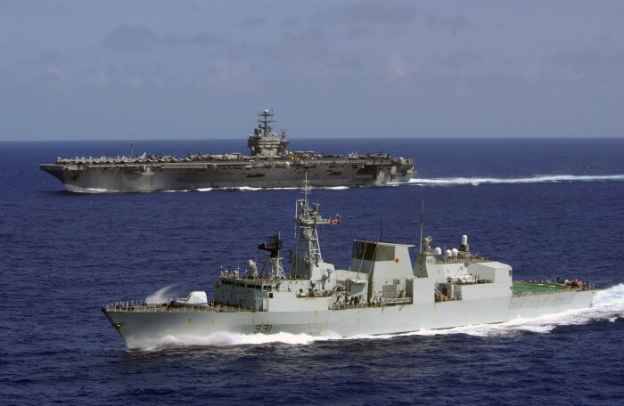 Canadian frigate HMCS Vancouver at sea, aircraft carrier in background