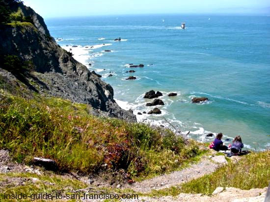 Two ladies sitting on cliff edge, Lands End trail