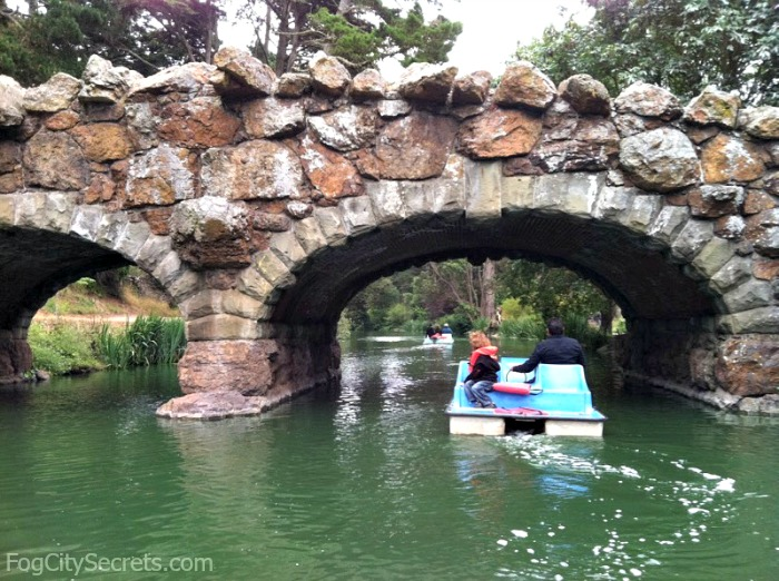 Paddle boat sailing under stone bridge at Stow Lake in Golden Gate Park